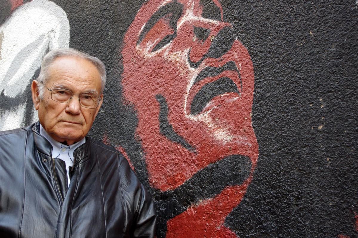 Joan Busquets, davant un mural llibertari en un carrer de Berga