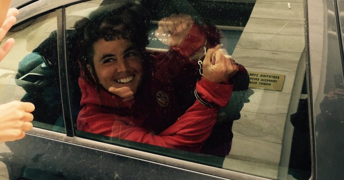Ariadna Masmitjà, saludant somrient emmanillada dins el cotxe de la policia grega que la van portar detinguda a comissaria