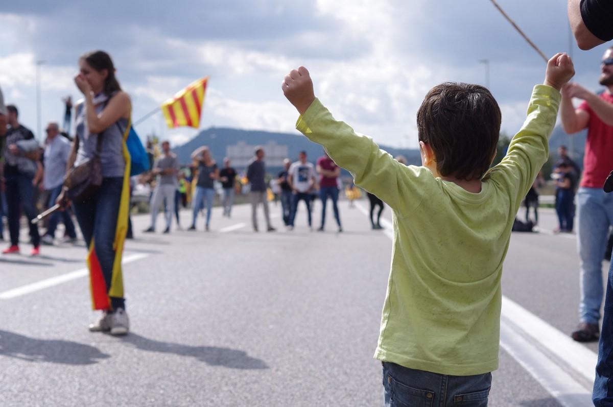 Un nen fent mostres d'eufòria al tall de la carretera
