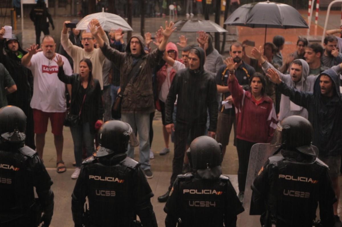 Persones defensant un dels col·legis de l'1-O davant la presència policial