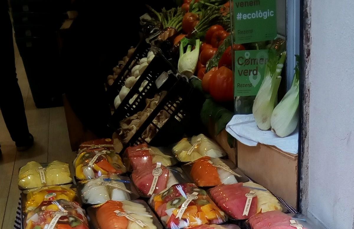 Safates de porexpan amb fruita en una botiga de productes ecològics de Gràcia