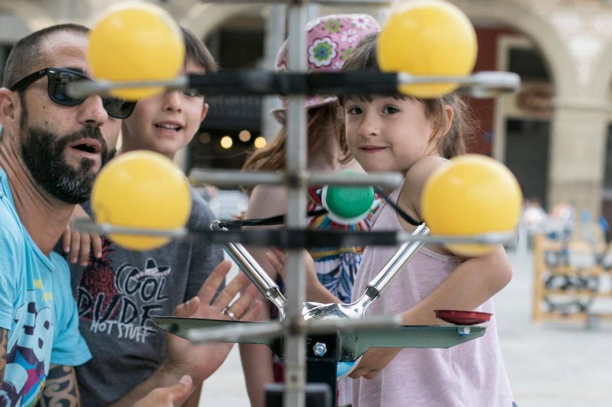 Nens -i adults- jugant amb els jocs fets a partir de material reciclat en el marc del programa «Joves i Reciclatge»