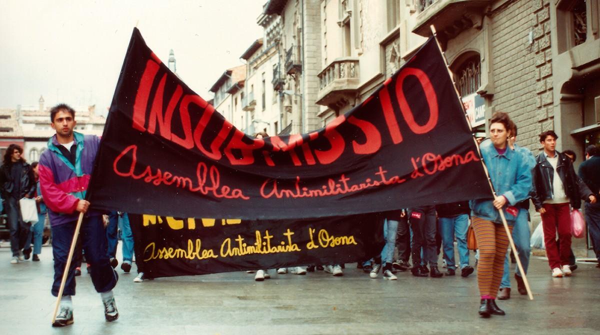 Manifestació de l'Assemblea Antimilitarista d'Osona a Vic a principis dels anys noranta. Aguantant la pancarta, Lluís Garcia i Mercè Sabata