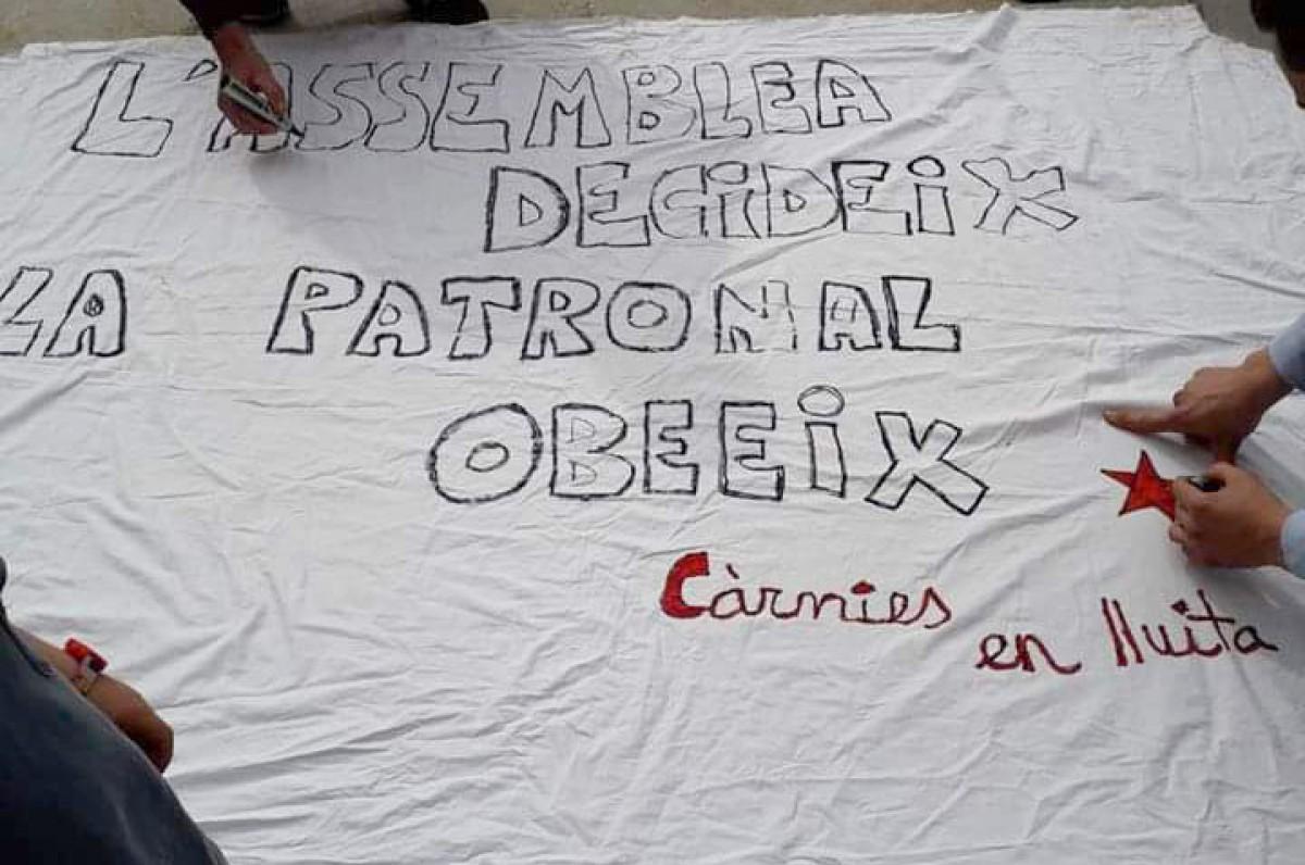 Pancarta per denunciar les condicions laborals de Le Porc Gourmet feta per alguns dels treballadors acomiadats per l'empresa, a la plaça Major de Vic