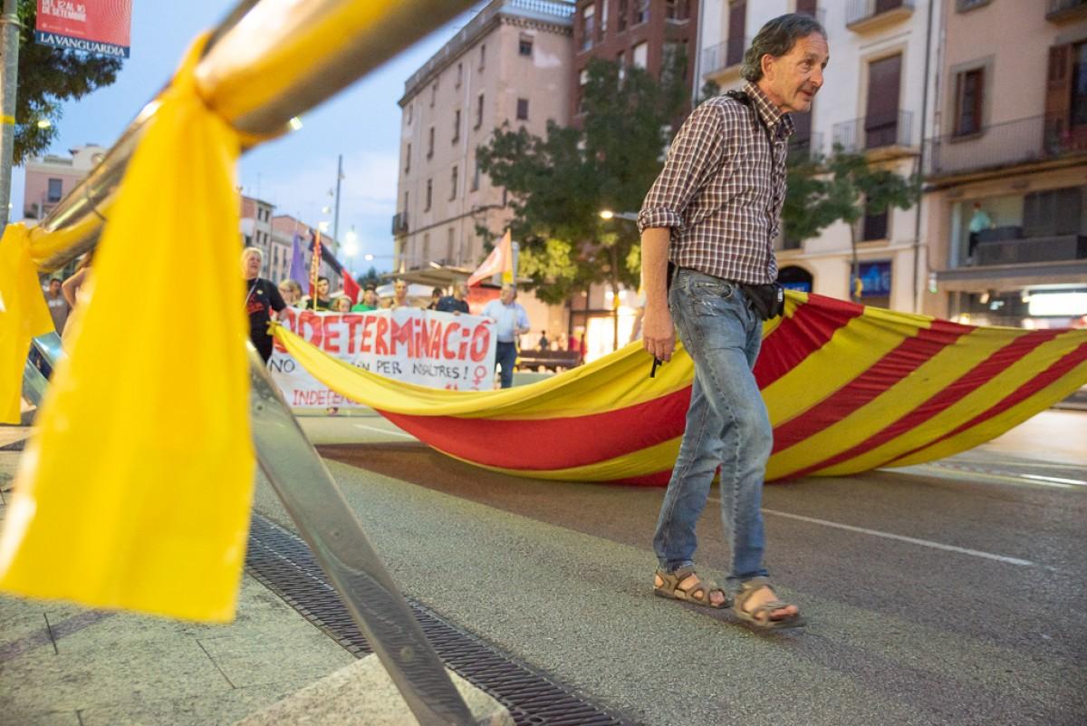 Ramon Ripoll aguantant l'estelada de la capçalera en una manifestació de la Diada a Vic