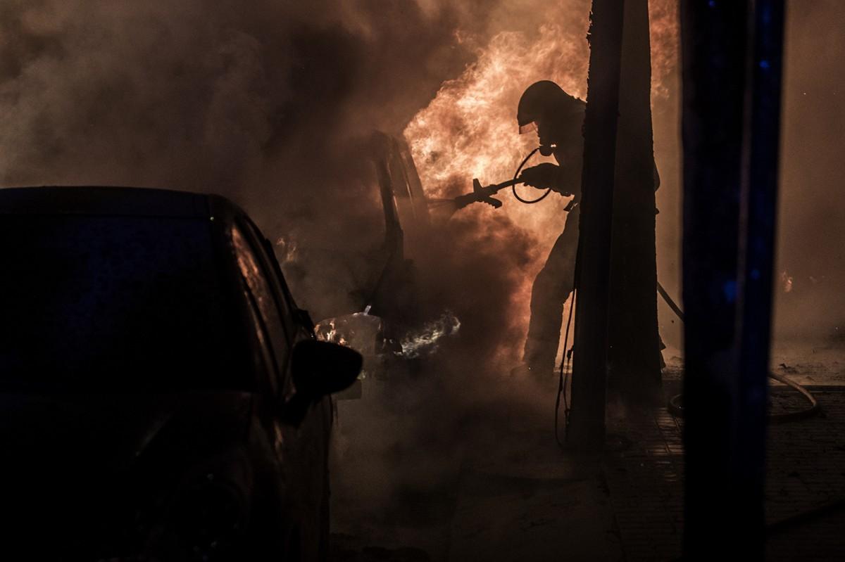 Un bomber apaga un dels focs originats durant les protestes d'aquesta setmana a Barcelona