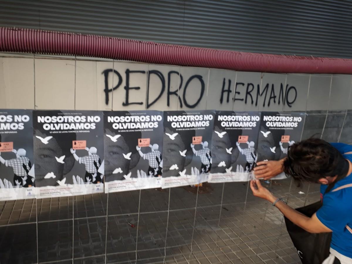 Un activista penjant cartells demanant justícia per a Pedro Álvarez amb motiu d'un dels aniversaris del seu assassinat