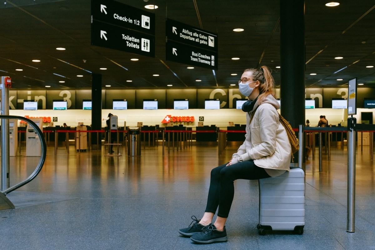 Un passatgera, solitària, espera en un aeroport en plena crisi sanitària