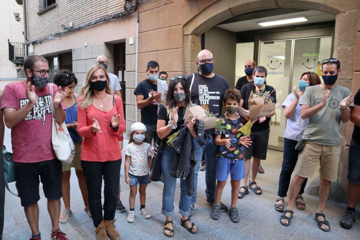 Sara Blázquez i Joan Coma, al centre de la imatge, amb altres membres de l'assemblea de Capgirem Vic que els van rebre amb un aplaudiment i un ram de flors a la sortida del ple d'aquest dilluns