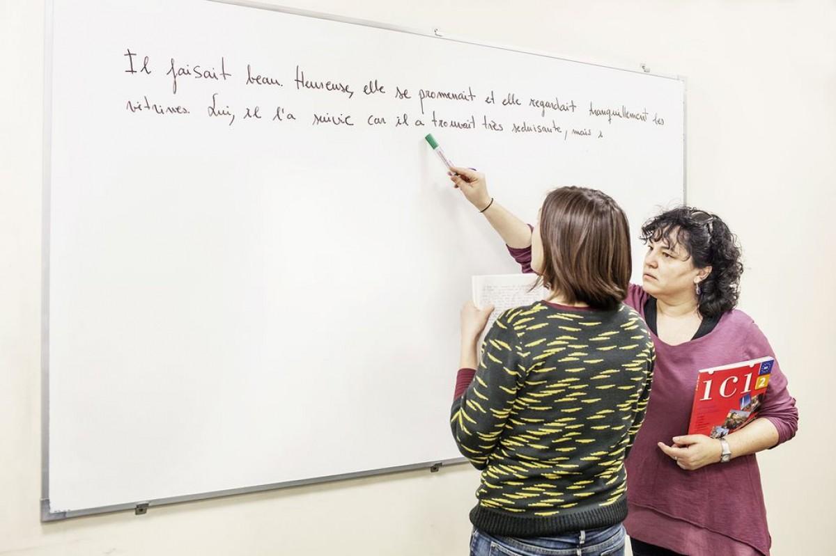Una professora i una alumna corregeixen un text en francès en una pissarra