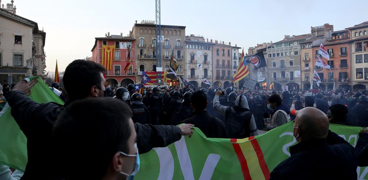 Membres de Vox, d'esquena a l'acte del seu partit, exhibint una pancarta en actitud provocativa als centenars de manifestants antifeixistes
