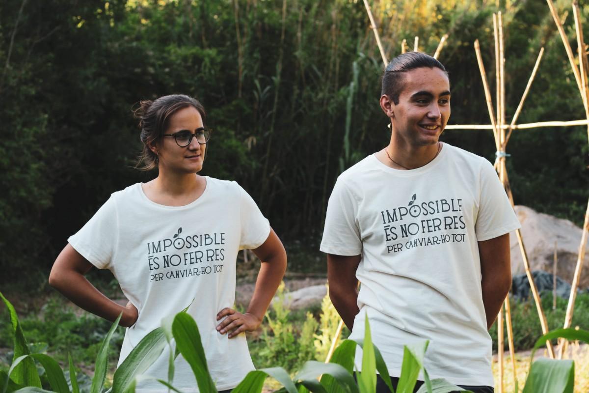 Dues persones als horts d'Eixarcolant amb la samarreta del lema de la campanya